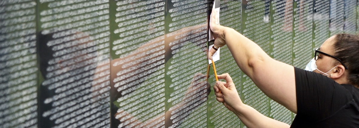 A visitor takes a rubbing of a name on a 3/4 scale replica of the Vietnam Memorial in Washington, D.C., on Friday. See below for more information and pictures. Photo by Randy Foster of New Bern Now